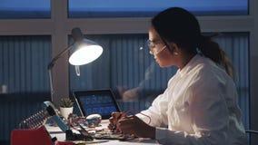 Engenheiro eletrónico fêmea que trabalham com verificador do multímetro e outros dispositivos eletrónicos no laboratório video estoque