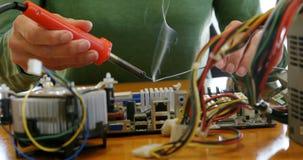Engenheiro eletrotécnico fêmea que solda uma placa de circuito 4k video estoque