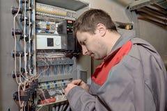 Engenheiro mecânico que faz o switchboa bonde do equipamento da elevação Fotografia de Stock Royalty Free