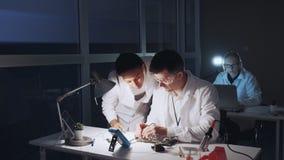 Engenheiros eletrónicos da raça misturada nos revestimentos brancos que trabalham no cartão-matriz usando o verificador do multím vídeos de arquivo