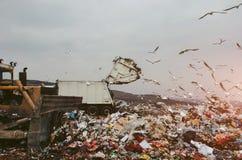 Engin de terrassement et camion à ordures sur une décharge image libre de droits