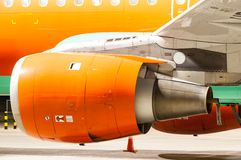 Engine of the airplane painted in orange. Close-up stock image