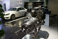 Engine in car dealership showroom. A automobile engine and cars at car dealership showroom Stock Photography