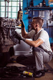 Engine check up. Mechanic is lifting engine for better inspection Stock Photo