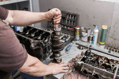 Engine crankshaft, valve cover, pistons. mechanic repairman at automobile car engine maintenance repair work.  Royalty Free Stock Images