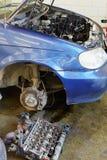 Engine cylinder head lies on floor near car Stock Photo