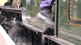 Engine driver climbing onto steam train  4K stock video