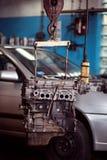 Engine hanging on automotive crane Stock Images