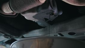 Engine oil under bottom of the car in garage workshop, close up. View stock video footage