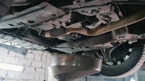 Engine oil under bottom of the car in garage workshop. Slider shot stock video footage
