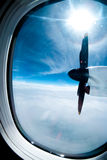 Engine and propeller of the plane, view from window airplane. White clouds and blue sky as background royalty free stock images