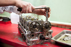 Engine repair. A hand with the wrench is repairing an engine Stock Images