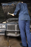 Engine repair with hammer Royalty Free Stock Photography