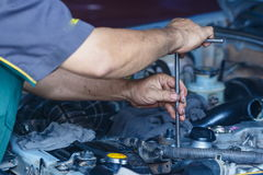 Engine repair,Mechanic working in a car under the hood. Engine repair,Mechanic working in a car under the hood,Engine repair service station Royalty Free Stock Photo