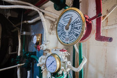 Engine Room Operation Gauge Commands. Operation gauge commands from pilot captain upstairs to engineer in engine room of a small steam tug harbor vessel with all Stock Image