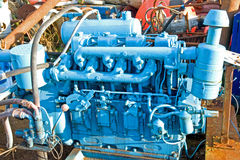 Engine in a scrap yard. A close up  image of a marine diesel engine painted blue in a scrap yard surrounded by discarded metal items Stock Photography