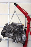 Engine In Shop For Rebuild. A car engine hanging from hoist in mechanic shop for professional tear down and rebuild.  Trade names and part numbers have been Stock Photo
