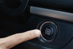 Engine start stop botton of car. With a finger Stock Photos