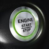 Engine Start and Stop Button, Automobile Starter. Close up of a metallic engine start and stop button, green light, blur effect, automotive starter concept Stock Images