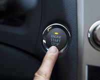 Engine start stop button of a car. Finger pressing the Engine start stop button of a car Stock Image
