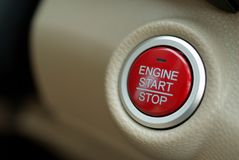 Car engine start button. Engine start stop button in modern car. Red button on beige leather background Royalty Free Stock Image