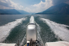 Engine and wake of motor boat speeding across lake surrounded by Stock Images