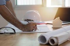 Enginee или чертеж и сочинительство архитектора на бумаге плана на столе, Стоковые Изображения RF