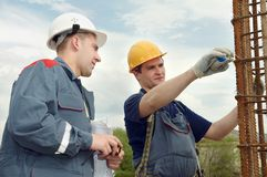 Engineer accept construction works. Two builders workers checking with measure tape reinforcement column Royalty Free Stock Photo