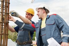 Engineer accepts construction works. Two builders workers checking with measure tape reinforcement column Stock Photo