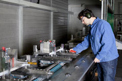 Engineer adjusts a machine in factory Stock Photography