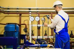 Engineer adjusts pressure sensors on industrial refinery plant royalty free stock photos