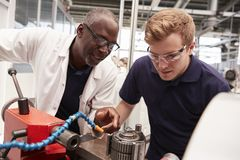 Engineer advising apprentice in factory, front view close up stock images