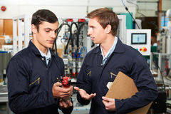 Engineer And Apprentice Discussing Component In Factory Stock Photos