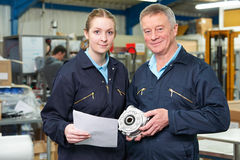 Engineer With Apprentice Looking at Component In Factory Stock Images