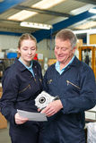 Engineer And Apprentice Looking At Component In Factory Stock Photo