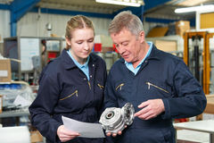Engineer With Apprentice Looking At Component In Factory royalty free stock photo