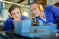 Engineer with apprentice using bench drill royalty free stock images