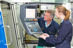 Engineer And Apprentice Using Computerized Cutting Machine Stock Photos