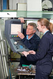 Engineer And Apprentice Using Computerized Cutting Machine Stock Photography