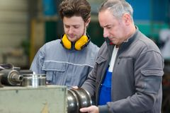 Engineer and apprentice using machinery in factory Stock Images