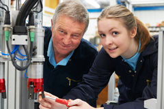 Engineer And Apprentice Working On Machine In Factory stock images