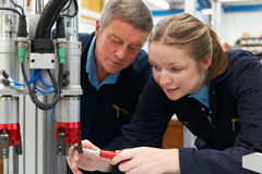 Engineer And Apprentice Working On Machine In Factory stock photography