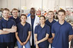 Engineer with apprentices in factory, group portrait royalty free stock image