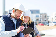Engineer and architect dating next appointment on a construction Royalty Free Stock Image