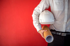 Engineer or Architect holding safety helmet and drawing Royalty Free Stock Images