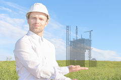 Engineer architect holds in hand mock-up of construction of apartment building. Royalty Free Stock Image