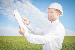 Engineer of architect points to drawings of project documentation at site of construction of property. Royalty Free Stock Photography