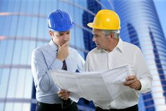 Engineer architect two expertise team plan hardhat. Architect engineer two expertise team plan talking hardhat skyscraper buildings royalty free stock photos