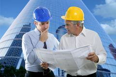 Engineer architect two expertise team plan hardhat. Architect engineer two expertise team plan talking hardhat skyscraper buildings royalty free stock photography