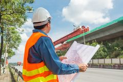 Engineer or Architect wear white Helmet working or reading Construction Plan. In Highway or Autobahn Construction site as Industrial or infrastructure stock image